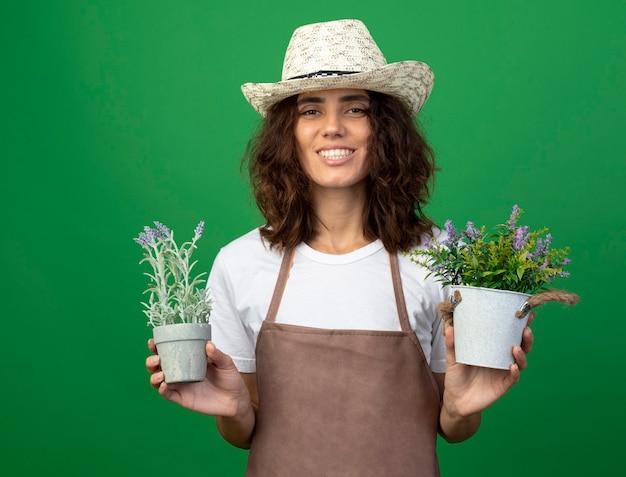 Uśmiechnięta młoda kobieta ogrodnik w mundurze na sobie kapelusz ogrodniczy trzyma kwiaty w doniczkach na białym tle na zielonej ścianie