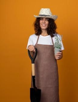 Uśmiechnięta młoda kobieta ogrodnik w mundurze na sobie kapelusz ogrodniczy trzyma łopatę z kwiatkiem w doniczce