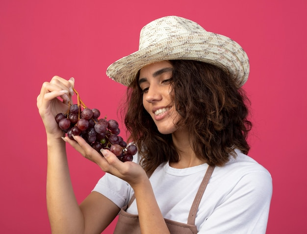 Uśmiechnięta młoda kobieta ogrodnik w mundurze na sobie kapelusz ogrodniczy, trzymając i patrząc na winogrona na różowym tle