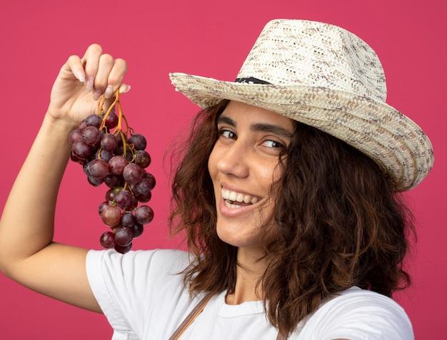 Uśmiechnięta młoda kobieta ogrodnik w mundurze na sobie kapelusz ogrodniczy trzymając winogrona na różowym tle