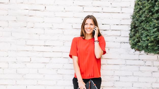 Uśmiechnięta młoda kobieta opowiada na smartphone przed ściana z cegieł