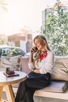 Uśmiechnięta młoda kobieta opowiada na telefonie komórkowym podczas gdy siedzący w caf�
