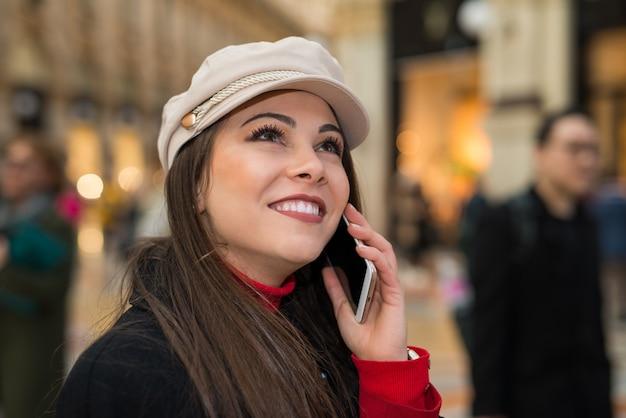 Uśmiechnięta młoda kobieta opowiada na telefonie komórkowym