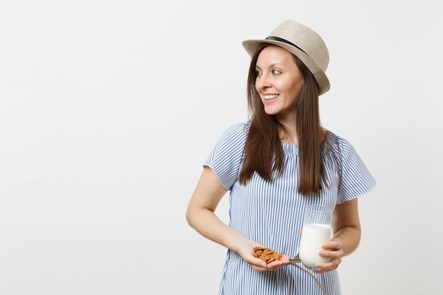 Uśmiechnięta młoda kobieta patrzeć na bok, trzymać w rękach mleko migdałowe w szkle, orzechy migdałowe na białym tle. prawidłowe odżywianie, wegański napój wegetariański, zdrowy styl życia, koncepcja diety. skopiuj miejsce.