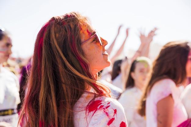 Uśmiechnięta młoda kobieta patrzeje daleko od z holi kolorem
