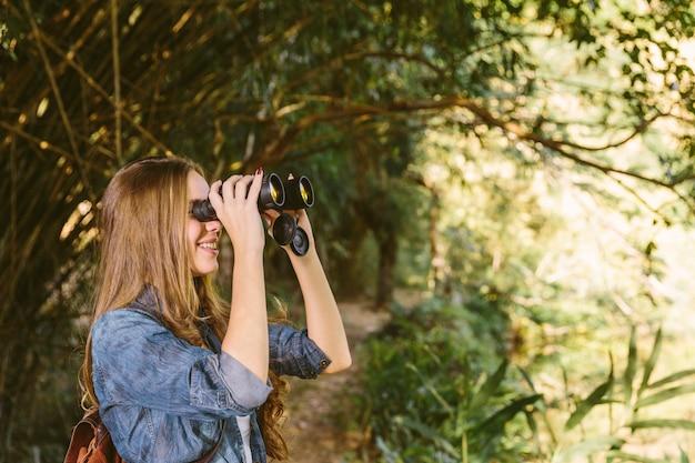 Uśmiechnięta młoda kobieta patrzeje przez lornetek w lesie
