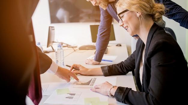 Uśmiechnięta młoda kobieta patrzeje wykres wskazującego jej kolegą na stole