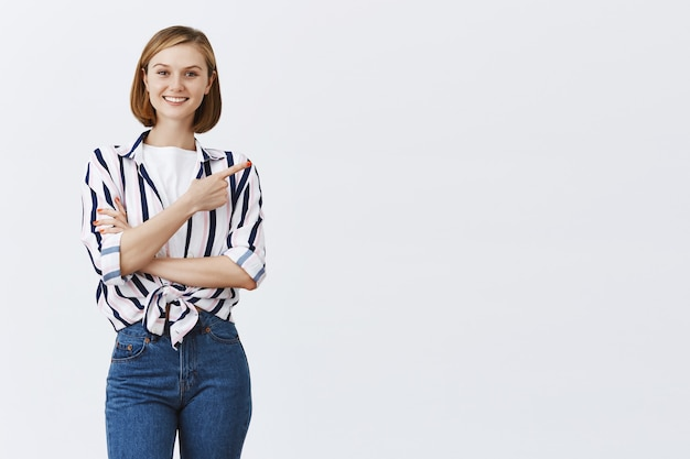Uśmiechnięta młoda kobieta pewnie, wskazując prawym górnym rogu na lato