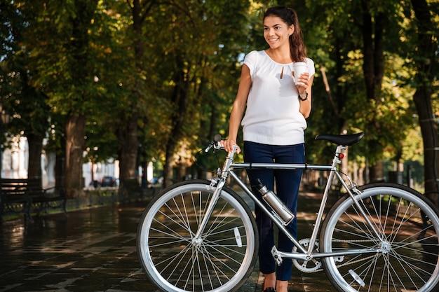 Uśmiechnięta młoda kobieta pije kawę na wynos i trzyma rower w parku miejskim