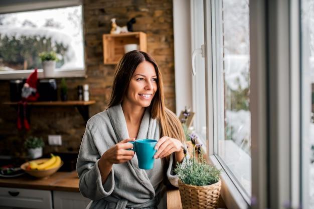 Uśmiechnięta młoda kobieta pije kawę rano w szlafroku, patrząc przez okno.