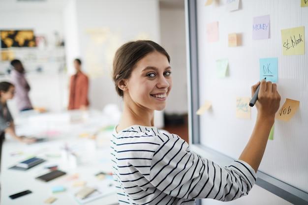 Uśmiechnięta młoda kobieta pisze na pokładzie