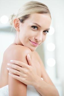 Uśmiechnięta młoda kobieta po prysznicu