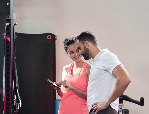 Uśmiechnięta młoda kobieta pokazuje coś na jej telefonie komórkowym brodaty młody człowiek na przerwie przy gym
