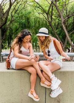 Uśmiechnięta młoda kobieta pokazuje jej telefon komórkowego jej żeński przyjaciel w parku