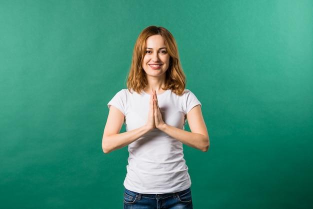 Uśmiechnięta młoda kobieta pokazuje namaste gest przeciw zielonemu tłu