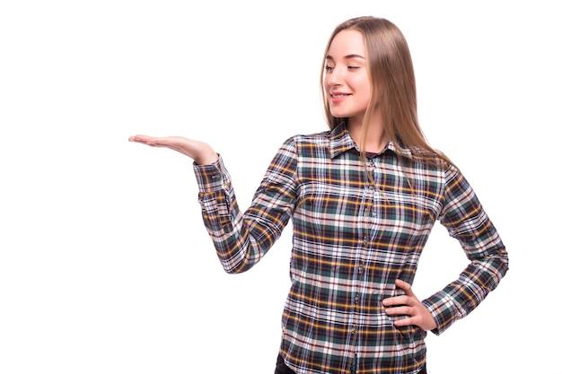 Uśmiechnięta młoda kobieta pokazuje otwartą dłoń z miejscem na kopię produktu lub tekstu