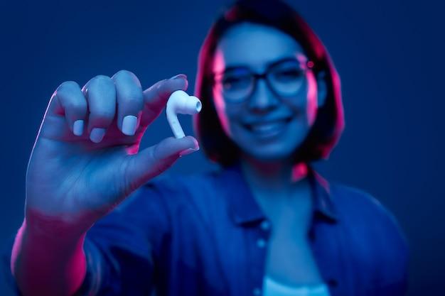 Uśmiechnięta Młoda Kobieta Pokazuje Słuchawki Premium Zdjęcia