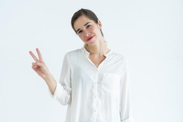 Uśmiechnięta młoda kobieta pokazuje zwycięstwo znaka, przechyla głowę kierowniczy i patrzeje kamerę.