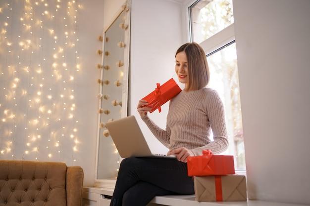 Uśmiechnięta młoda kobieta pozdrowienia przyjaciół z bożym narodzeniem w czacie wideo na laptopie z pudełkami