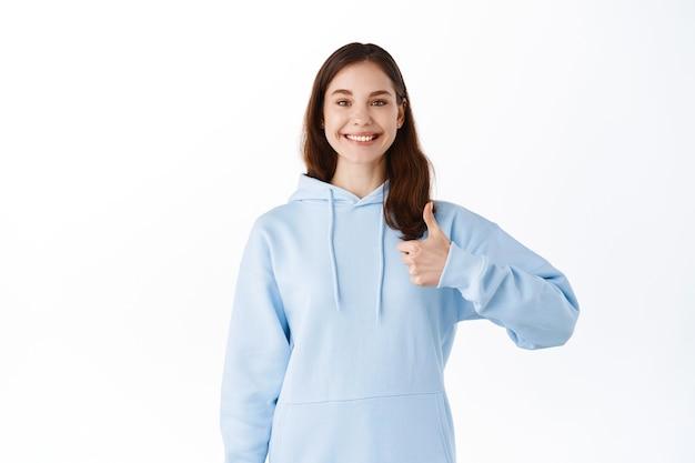Uśmiechnięta młoda kobieta pozostaje pozytywna, zachęca, chwali lub daje gwarancję, pokazuje kciuki w górę w aprobacie, stoi przy białej ścianie