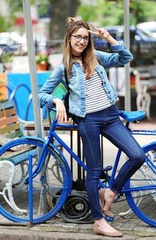 Uśmiechnięta młoda kobieta pozuje z rowerem