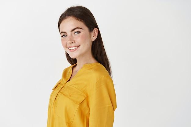 Uśmiechnięta młoda kobieta, pracownik biurowy patrzący pewnie na kamerę, stojący nad białą ścianą