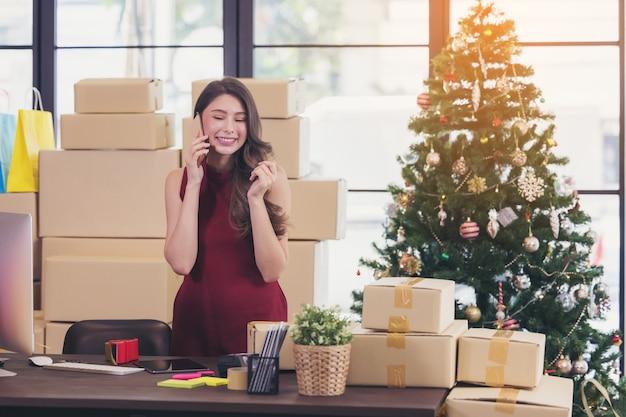 Uśmiechnięta młoda kobieta pracuje w domu i rozmawia na smartfonie