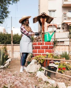 Uśmiechnięta młoda kobieta przycina rośliny na handmade well
