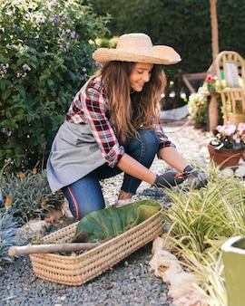 Uśmiechnięta młoda kobieta przycina rośliny w jarzynowym ogródzie
