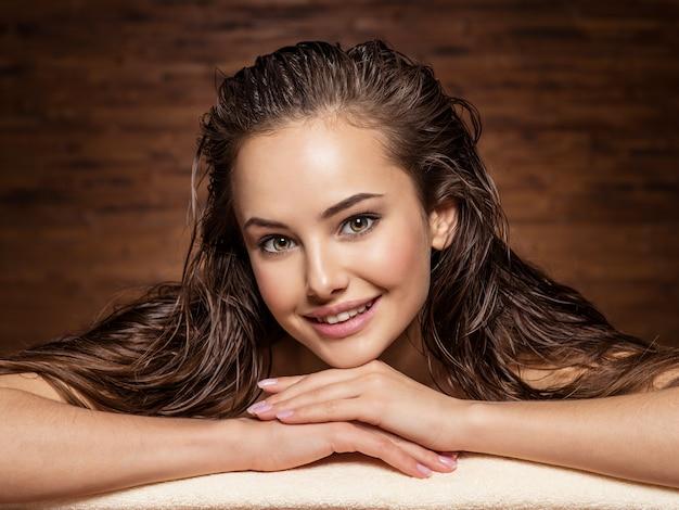 Uśmiechnięta młoda kobieta relaks w salonie spa. zabieg upiększający. pielęgnacja włosów