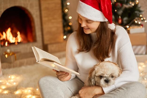 Uśmiechnięta młoda kobieta relaksująca się przy kominku, czytająca książkę w przytulnej świątecznej atmosferze z ozdobionym drzewkiem bożonarodzeniowym, pani patrząca na strony ze skupionym spojrzeniem, przytulająca psa.