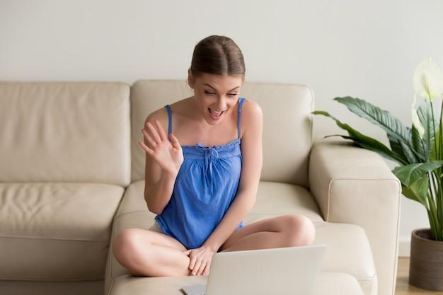 Uśmiechnięta młoda kobieta robi dystansowej wideo wezwaniu na laptopie