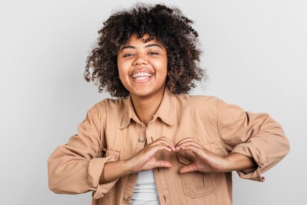 Uśmiechnięta młoda kobieta robi paleniska znakowi