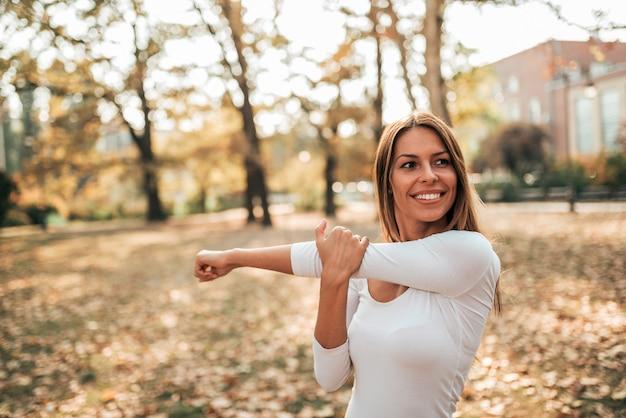 Uśmiechnięta młoda kobieta robi rozciągliwość ćwiczy w parku.
