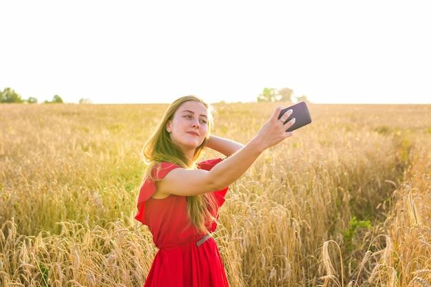 Uśmiechnięta młoda kobieta robi selfie przez smartfona na polu zbóż