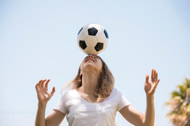 Uśmiechnięta młoda kobieta równoważenia piłki nożnej na czole