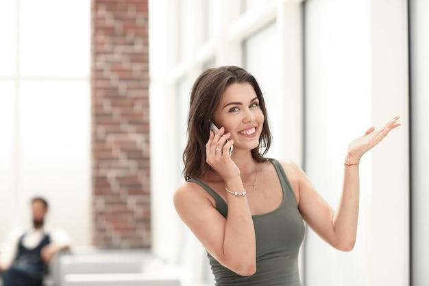 Uśmiechnięta młoda kobieta rozmawia przez telefon komórkowy.