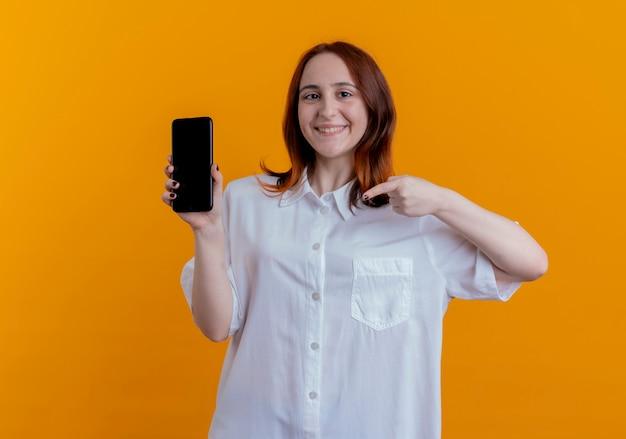 Uśmiechnięta młoda kobieta rude gospodarstwa i wskazuje na telefon na żółtym tle
