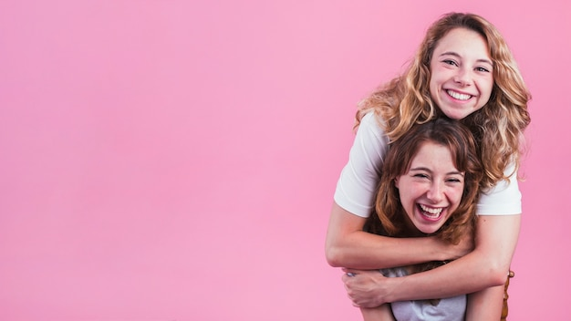 Uśmiechnięta młoda kobieta ściska jej przyjaciela od behind przeciw różowemu tłu