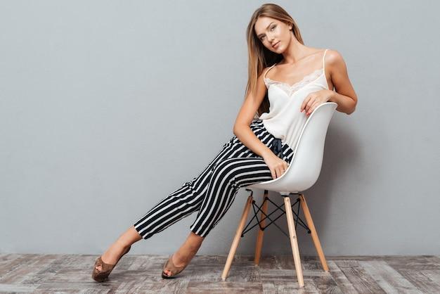 Uśmiechnięta młoda kobieta siedzi na krześle na białym tle na szarym tle