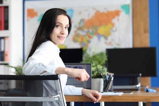 Uśmiechnięta młoda kobieta siedzi w miejscu pracy zbliżenie