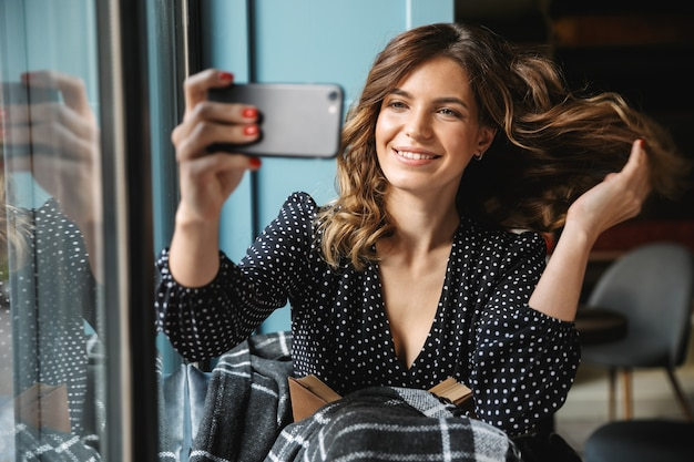 Uśmiechnięta młoda kobieta siedzi zawinięty w koc przy oknie, biorąc selfie