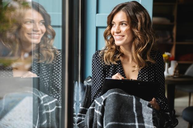 Uśmiechnięta młoda kobieta siedzi zawinięty w koc przy oknie, robiąc notatki