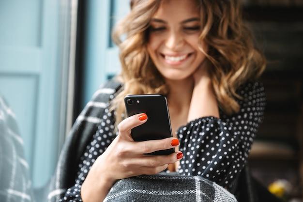 Uśmiechnięta młoda kobieta siedzi zawinięty w koc w oknie, przy użyciu telefonu komórkowego