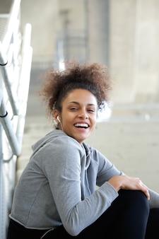Uśmiechnięta młoda kobieta słucha muzyka z słuchawkami