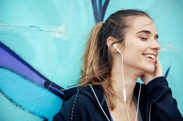 Uśmiechnięta młoda kobieta słucha muzyka z smartphone i hełmofonami