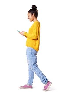 Uśmiechnięta młoda kobieta spaceru i patrząc na telefon komórkowy