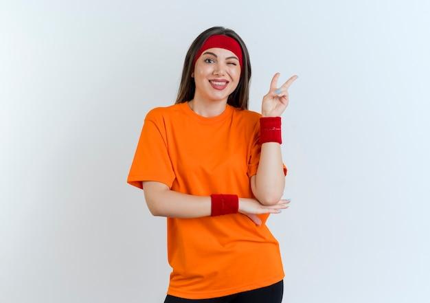 Uśmiechnięta młoda kobieta sportowy noszenia opaski i opaski na rękę kładąc rękę pod łokciem mrugając robi znak pokoju patrząc na białym tle