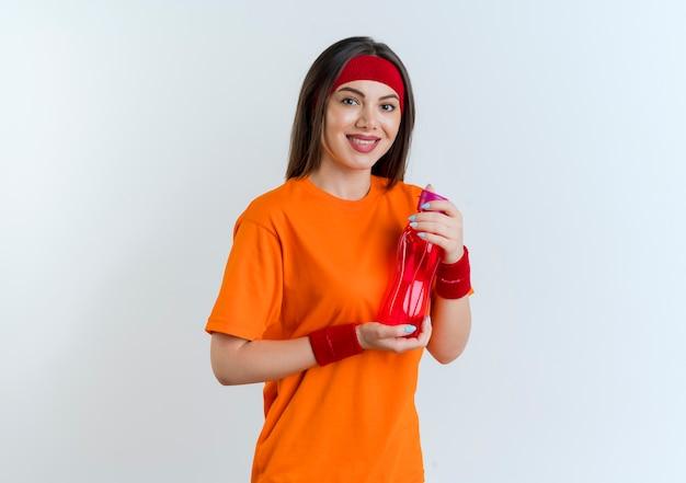Uśmiechnięta młoda kobieta sportowy noszenie opaski i opaski na rękę trzymając butelkę wody patrząc na białym tle