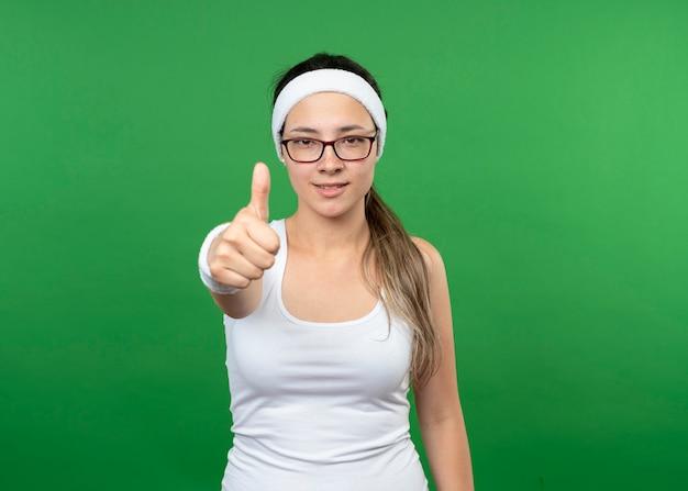 Uśmiechnięta młoda kobieta sportowy w okularach optycznych na sobie opaskę i opaski kciuki do góry na białym tle na zielonej ścianie